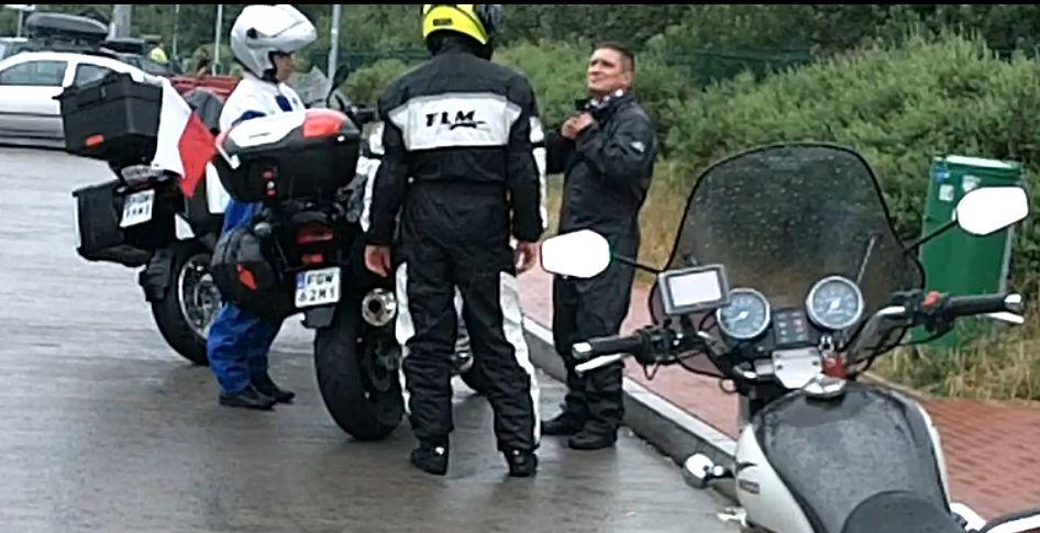 Drei Leute stehen um die Motorräder, einer macht seinen Regenanzug noch zu.