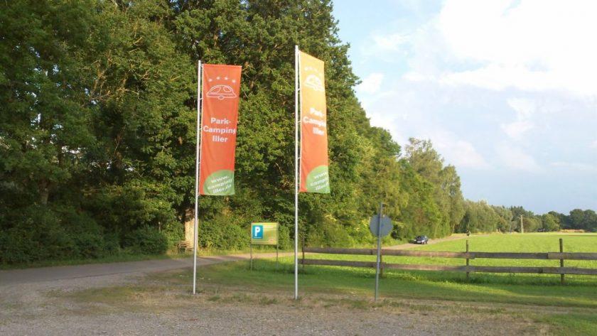 Zwei große Werbefahnen senkrecht an Fahnenmasten mit WIese und Waldweg.